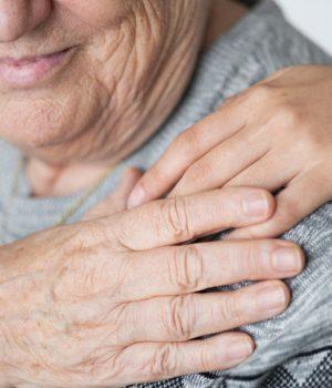 person holding elderly's shoulder